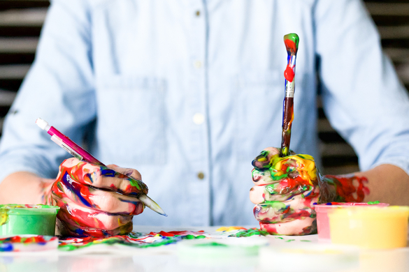 Man holding painbrushes covered in messy paint
